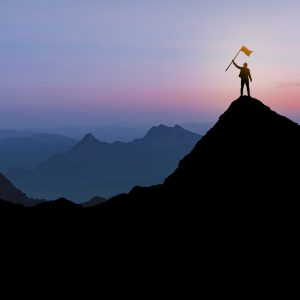 Silhouette of Businessman standing on mountain top over sunrise twilight background with flag, Winner, Success and Leadership concept